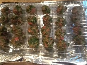 Meatballs on a lined baking sheet with a cookie cooling grate that is oven proof